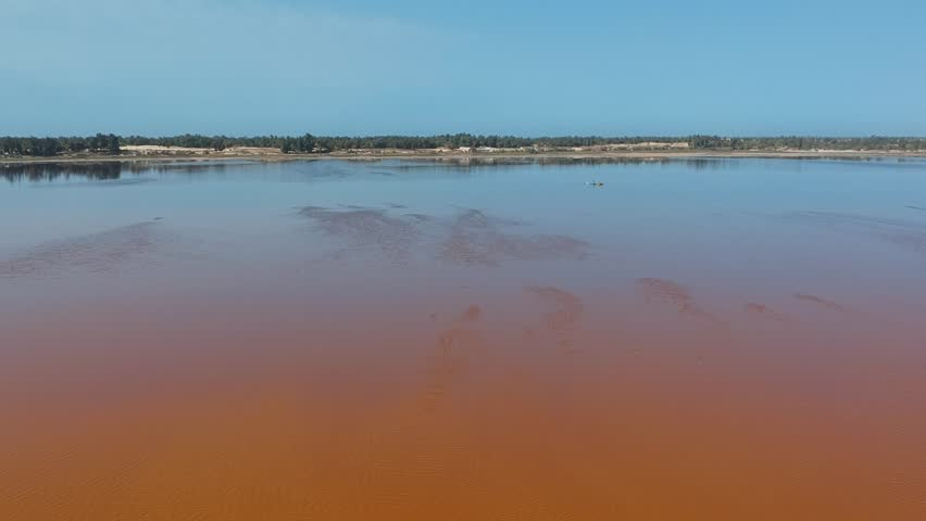 Aerial view of Lac Rose or Lake Retba in Senegal. Pink lake showing natural beauty and rich color on a sunny day. View of lake coastline and atlantic in the background.