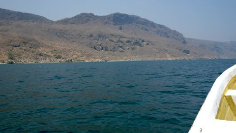 Speeding along the coast of Oman near Salalah in a small boat looking towards the coastline in point of view style