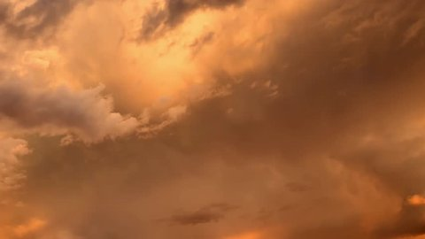 Richly colored clouds during an active storm sunset. A time lapse of the large orange sunset as the massive sun sets into the horizon above the ocean, Sunset sky clouds. Sunset sky background. 4K.