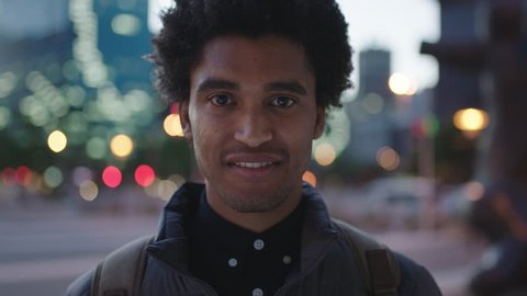 Close up portrait of handsome young mixed race man laughing cheerful at camera enjoying calm urban evening in city commuting travel lifestyle