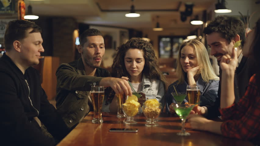 Group of friends are drinking, eating snacks and talking while sitting at table in bar. Young people enjoying themselves and communicating in pub concept. | Shutterstock HD Video #1010554466