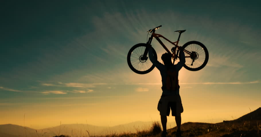 Mountain biker reaching the top celebrating with lifting his bike to the sky in amazing sunset light. #1010578226