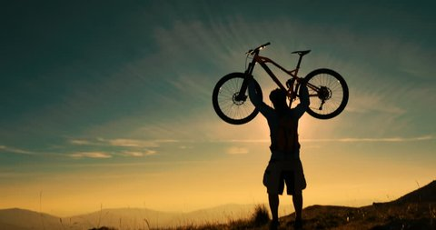 Mountain biker reaching the top celebrating with lifting his bike to the sky in amazing sunset light.