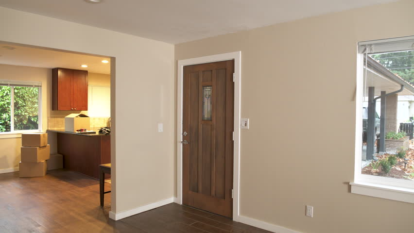 Couple walking through front door of new home, woman blindfolded and surprised.