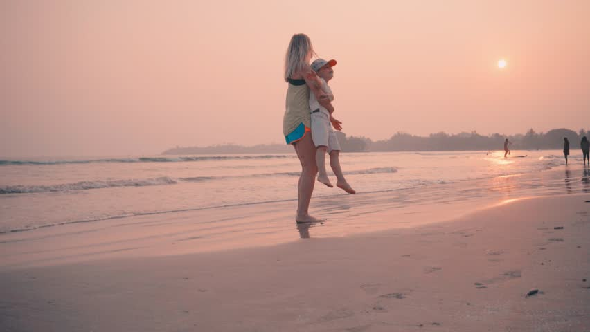 Mother and son walking on the ocean beach under Sunset in sunny day. Seascape view with palms. | Shutterstock HD Video #1010615066