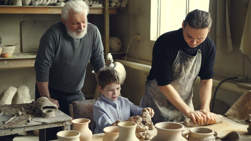 Professional potter is kneading clay on worktable in home studio while his son is helping him and his elderly father watching them from behind. Small family business concept.