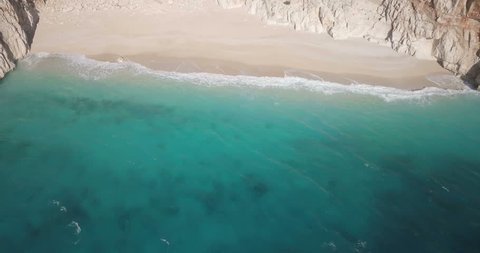 Reverse aerial drone video sand beach, turquoise water pull out to reveal Kaputas Beach and cliffside highway near Kas, Turkey. 4k at 23.97fps