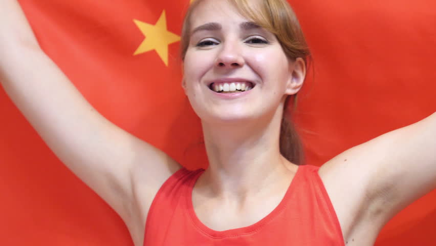 Chinese Young Woman Celebrating while holding the Chinese Flag in Slow Motion