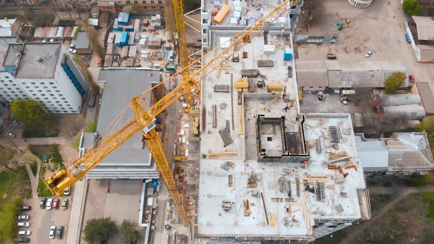 Construction site with a bird's eye in a megacity. Video shooting with drone. New house in a new residential complex. Flying over the construction site. New house next door in the city. 4K. | Shutterstock HD Video #1010662256