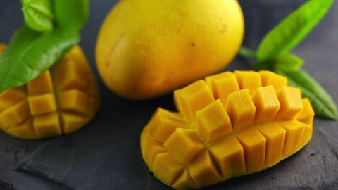 Organic tropical fruits, close up slides mangoes on black plate. Focus shift and rotate.