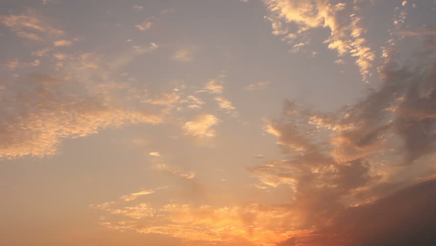 Golden colored clouds from sunlight of sunset darkening in twilight sky
