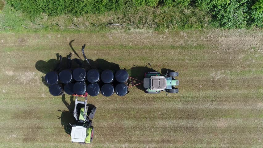 Aerial top down view of farmers picking up fodder animal feed for domesticated livestock such as cattle fodder is also called provender and includes hay straw and silage 4k high resolution footage