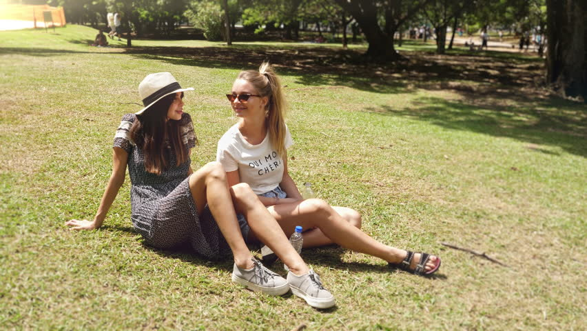 Young women relaxing together on grass in park #1010739716