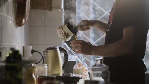 Man Pouring Steaming Fresh Made Coffee In A Coffee Cup