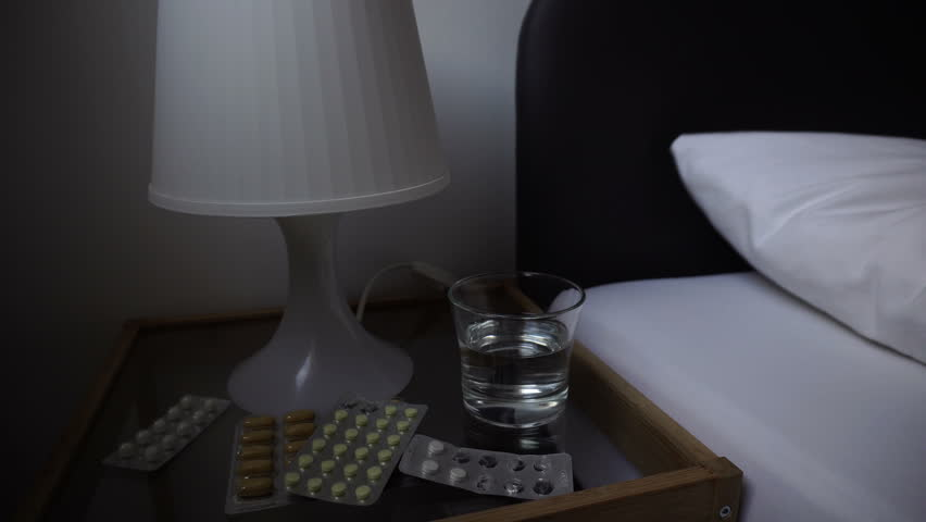 Self-medication concept. Sick man sleeping bad in bed at home, a lot of pharmacy and glass of water on bedside table in bedroom. This is flu, headache. Morning or night time.