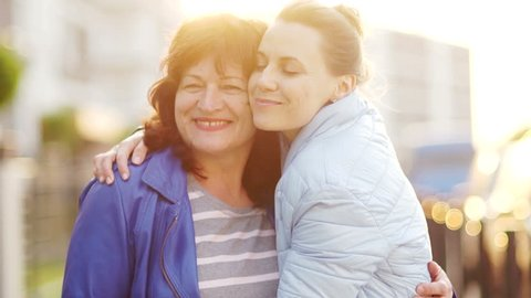 A mature mother and an adult daughter met on the street and embrace. Happy family, continuity of generations. Mothers Day