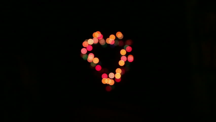 Christmas lights colored with many colors in progressive turning on and off, on a black background, to form a decorative frame in the shape of a heart. | Shutterstock HD Video #1010798576