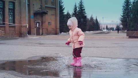 Cinemagraph: little child is jumping in a puddle, leaving a lot of spray