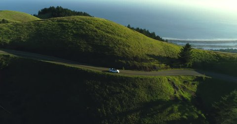Aerial view of car driving down country road in rural rolling hills with ocean in background at sunset