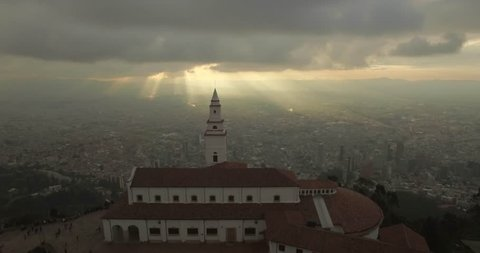 Sunset aerial flying over Monserrate Church in Bogota Colombia with the city below