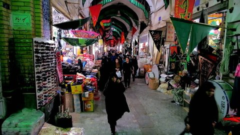KASHAN, IRAN - OCTOBER 22, 2017: Busy alleyway of old Grand Bazaar, decorated with flags of Muharram Festival, locals walk along the stores of household goods and food stalls, on October 22 in Kashan