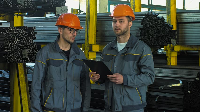 Two male metalworkers having a short meeting at the factory storage. Warehouse workers checking inventory together. Heavy industry workers examining documents. Occupation, development, industrial conc
