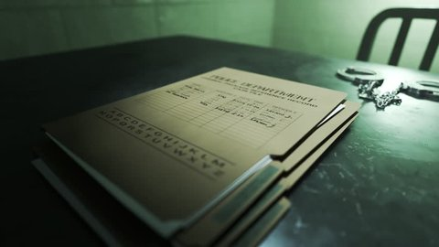 Closeup of metal handcuffs and case files on a table in the interrogation room