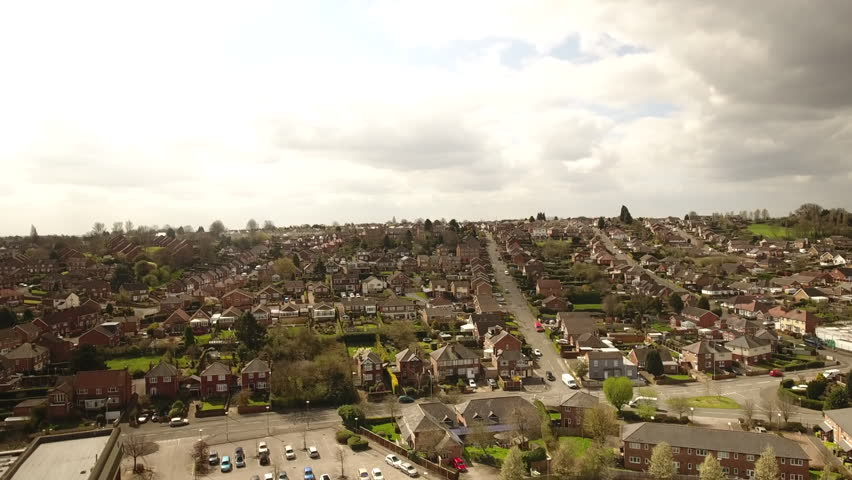 Aerial footage over a classic British housing estate, English houses and homes. Middle class and council properties on a cloudy day.