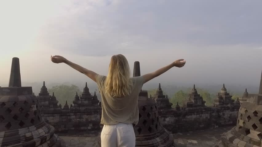 SLOW MOTIOM video of young woman wandering and running in Borobudur ancient buddhist temple at sunrise. People travel discovery Asia concept