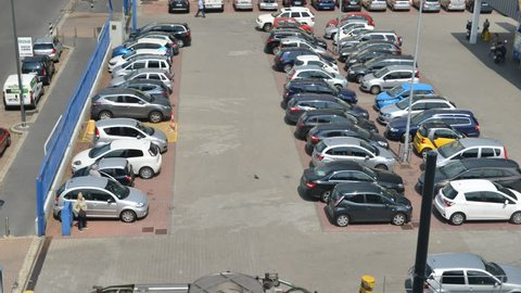 Aerial Time lapse of a people and cars at a busy parking lot during the day.