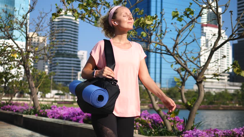 Fitness Woman Walking In City Park With Yoga Mat Wearing Wireless Earphones