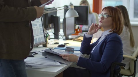Disabled business woman sitting in wheelchair at desk and discussing financial documents with male colleague in office