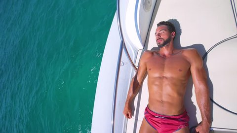 Young and strong man relaxed in yatch