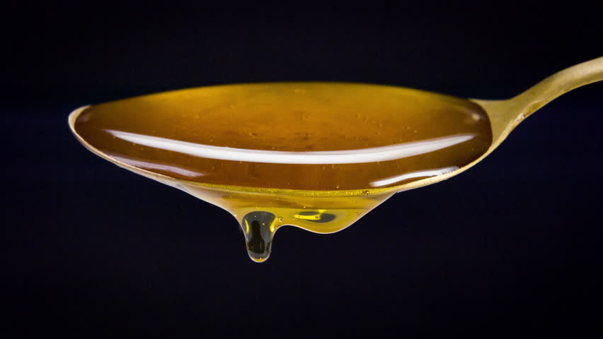 Sweet honey spilling over the spoon stock video close up shoot
