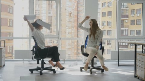 Office workers, two young women sitting on a chair holding documents in hands happily spinning on a chair in a circle laughing and spreading sheets of paper