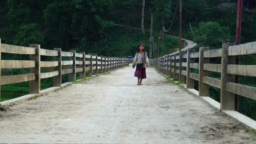 SAPA, VIETNAM - May 8, 2018: orphan child girl kid walking in nature on a beautiful bridge in Sa Pa, Vietnam, Asia