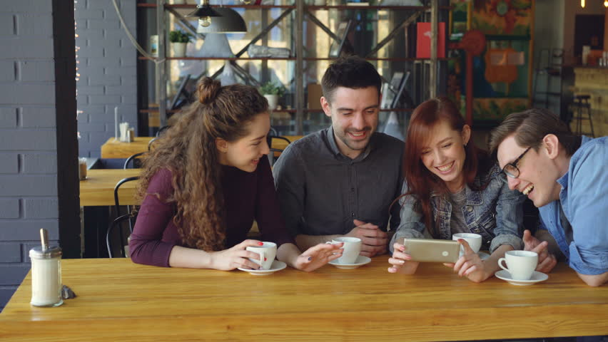 Good-looking friends are watching interesting video and discussing it while drinking tea at table in cozy cafe. Modern lifestyle and happy people concept.