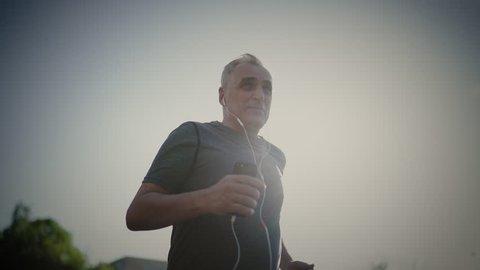 Senior seventy years old man jogging at sunset. Evening running