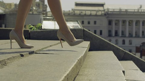 Perfect slim female legs in trendy high heel shoes stepping down on stairway in the city on sunny day over amazing urbanscape bacground. Elegant woman in high heels walking down staircase. Close-up.
