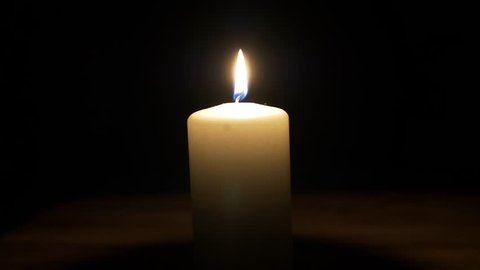 Lit white wax candle burning in a dark room - close up