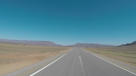 Seamless looping motion blure POV driving shot on an empty road in northern Africa, Morocco