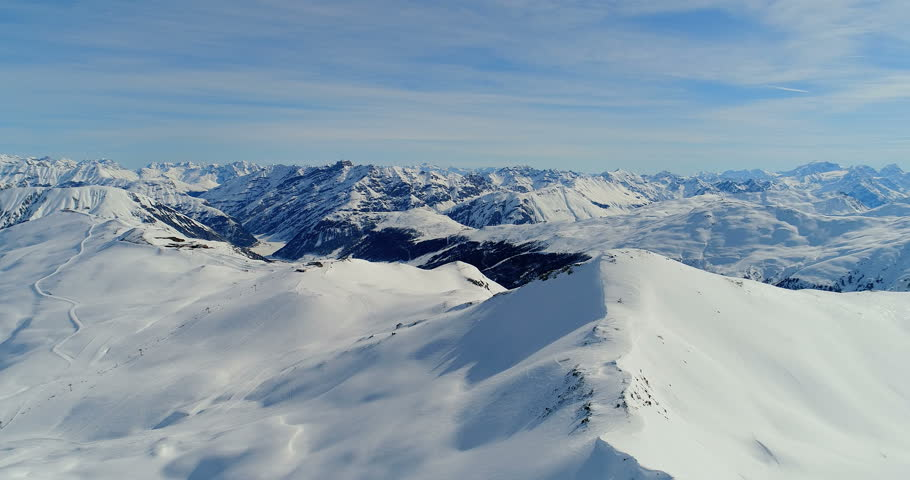 flying near rocky mountains covered with snow - Livigno, alps