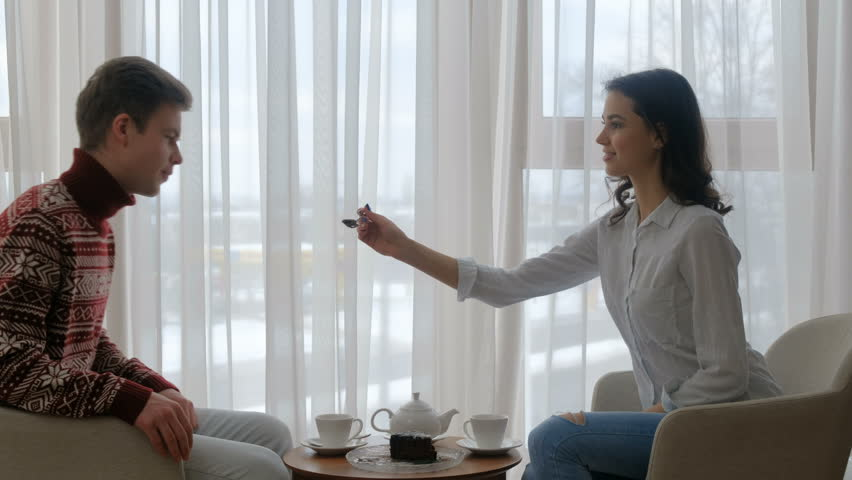 couple home leisure. man and woman drinking tea. girl feeding cake to a guy. care and love concept | Shutterstock HD Video #1010962766