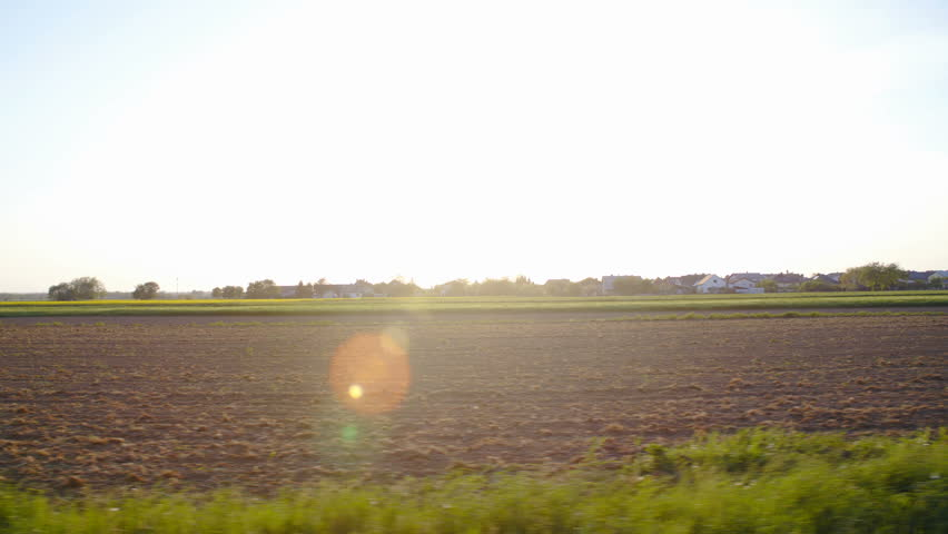 Car side window view of empty farmland sun flares shine 4K. Wide shot of fresh soil field in focus with sunset shining in background making sun flares over frame. | Shutterstock HD Video #1010999816