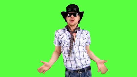 Cheerful cool cowboy in a hat and sunglasses is dancing jokingly, singing and enjoying. Actor performing on the green background.