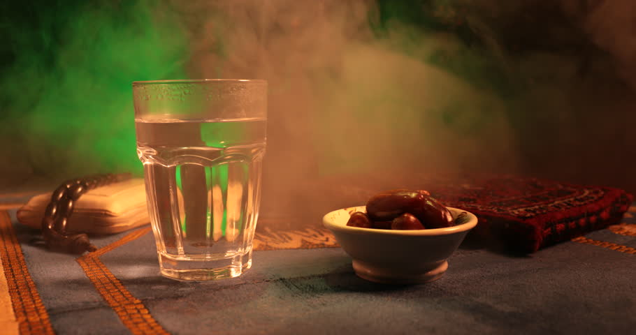 Water and dates. Iftar is the evening meal. Slider view of decoration Ramadan Kareem holiday. Festive greeting card, invitation for Muslim holy month Ramadan Kareem. Dark background. Selective focus | Shutterstock HD Video #1011034766