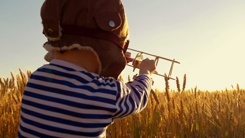 Happy child playing with toy airplane on wheat field on sunset background. The boy shows the flight of the plane, in a slow motion