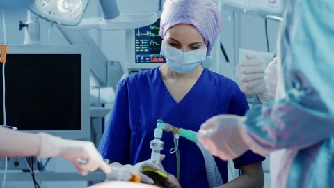 In the Hospital Operating Room Anesthesiologist Applies Anesthesia Mask to a Patient, Assistants Disinfects with Iodine place of Incision, Surgeons Wait to Start Surgery.