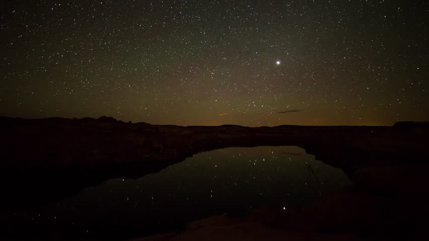 Time lapse of the moon rising over lake in the desert viewing stars reflecting in Lake Powell in Utah.