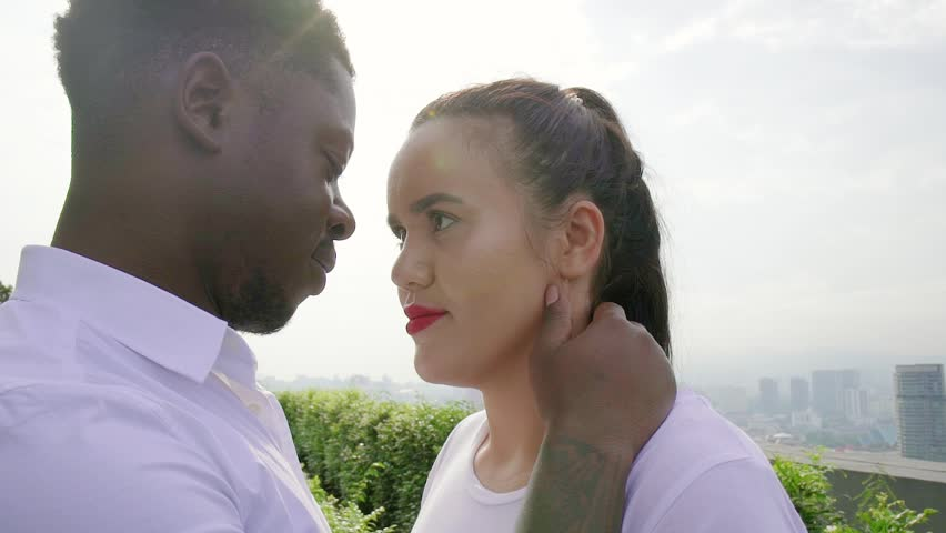 Close up of attractive multiethnic couple having moment of tenderness, looking at each other in the sun light. Sexy asian young woman and handsom african american man on the roof top.
